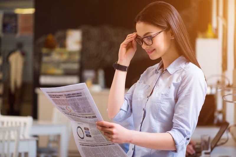 Eine Frau sucht in der Zeitung nach einem Zweitjob