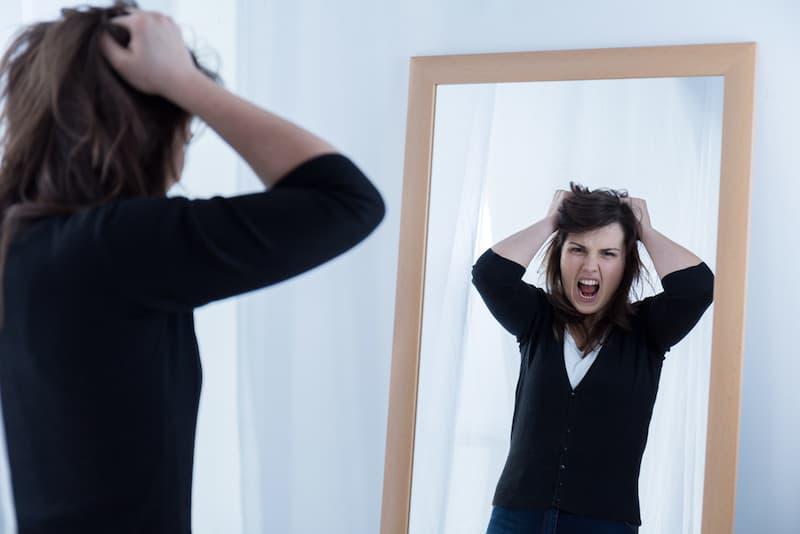 Eine Frau schreit ihr Spiegelbild an, ein Symbolbild für Selbstkritik