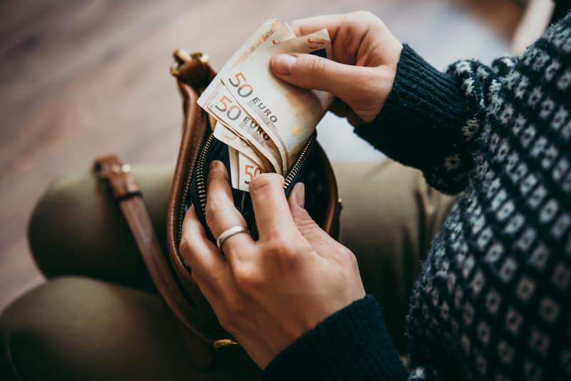 Eine Frau hat aufgrund des Sonntagszuschlags mehr Geld im Portemonnaie