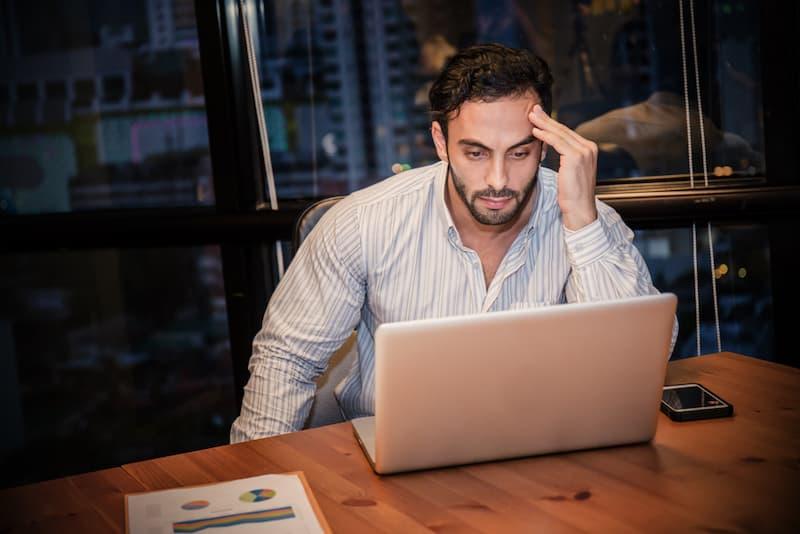 Ein Mann sitzt gestresst vor dem Laptop, er steckt in einem Teufelskreis