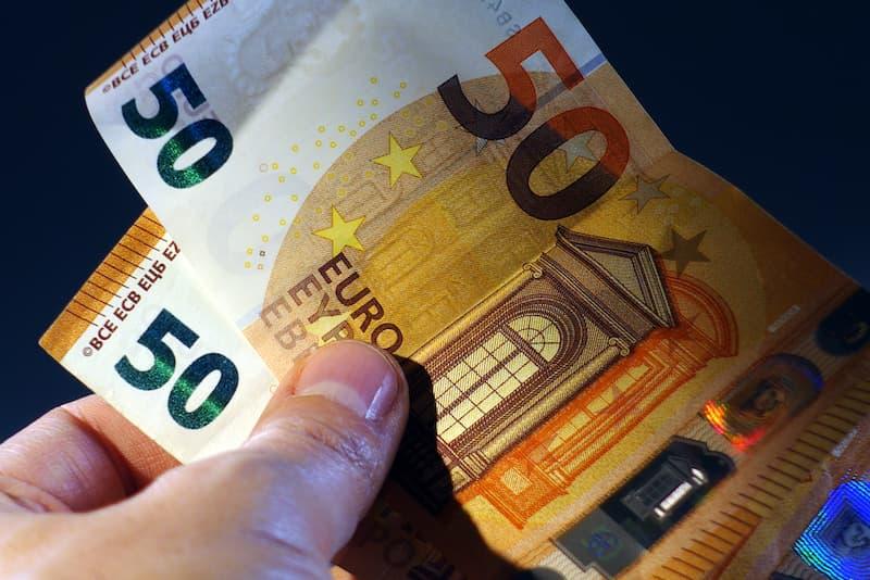 Eine Hand hält mehrere Geldscheine, ein Symbolbild für Lohndumping