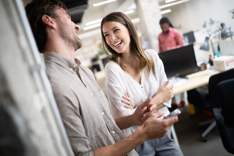 Eine Frau und ein Mann lachen im Büro, es herrscht eine gute Arbeitsatmosphäre