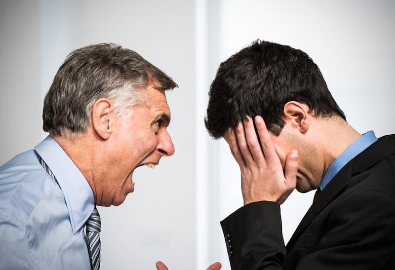 Ein Chef brüllt seinen Mitarbeiter an und betreibt Bossing