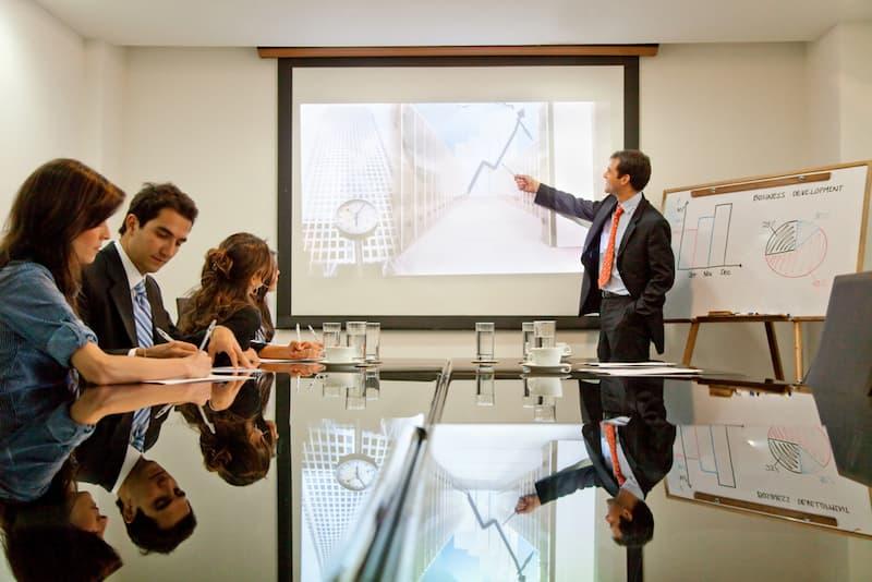 Ein Chef zeigt in einem Meeting auf eine Infografik, die Mitarbeiter erhalten eine Gewinnbeteiligung
