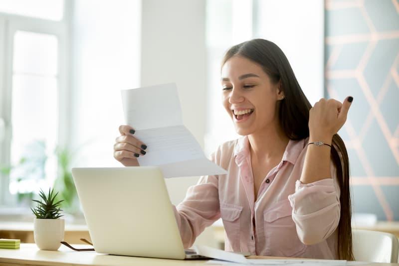 Eine Frau hält einen Brief und freut sich, sie kann ihre Ausbildung verkürzen