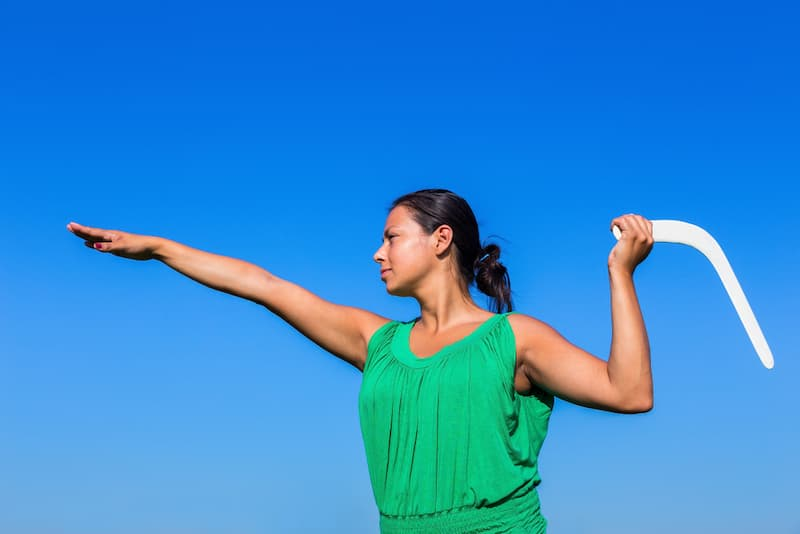 Eine Frau wirft einen Bumerang, dieser steht symbolisch für den Bumerang-Effekt