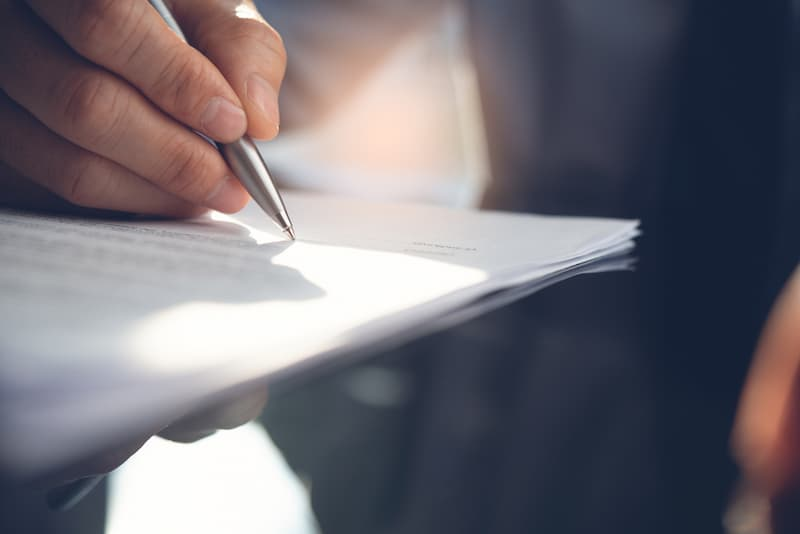 Ein Mann unterschreibt einen Freelancer-Vertrag